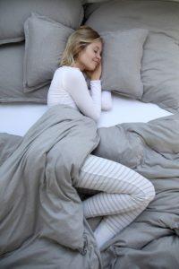 Jeune femme enroulée dans housse de couette
